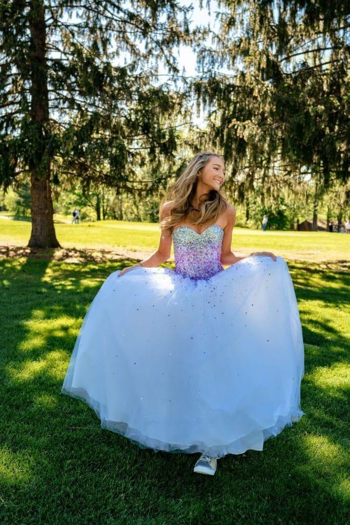 girl holding dress under trees
