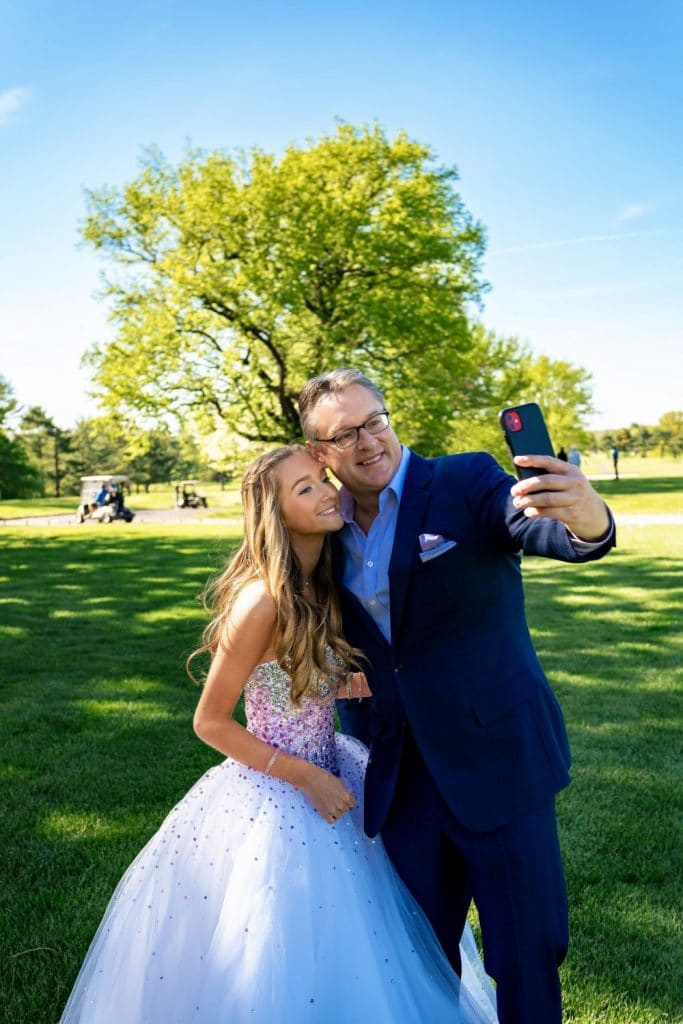 father and daughter taking selfie together