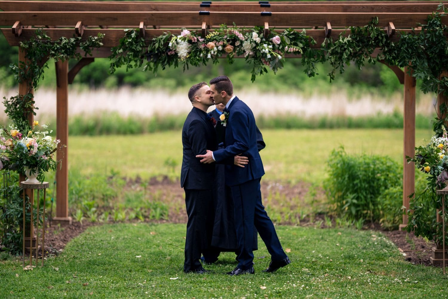 Grooms sharing kisses under the awn