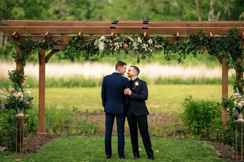 Beautiful grooms loving gazing at each other under awn Bishop Farmstead Wedding shot by John Ryan