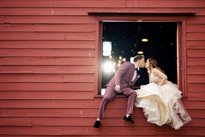 Sitting in Red Barn window Bishop Farmstead Wedding shot by John Ryan