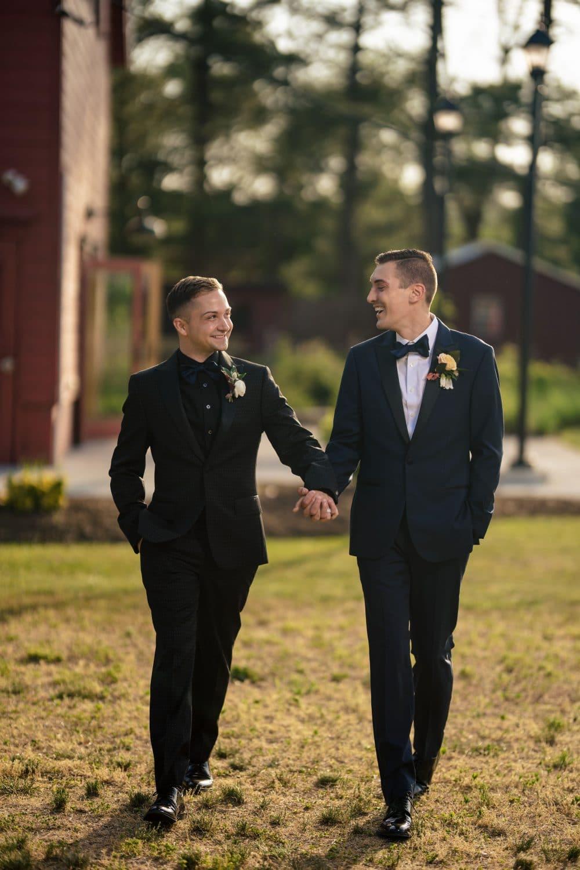Grooms walking hand in hand on farm Bishop Farmstead Wedding shot by John Ryan