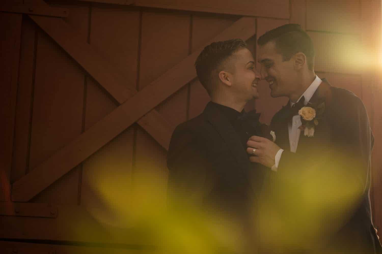 Dana and Sean in love near red barn house Bishop Farmstead Wedding shot by John Ryan
