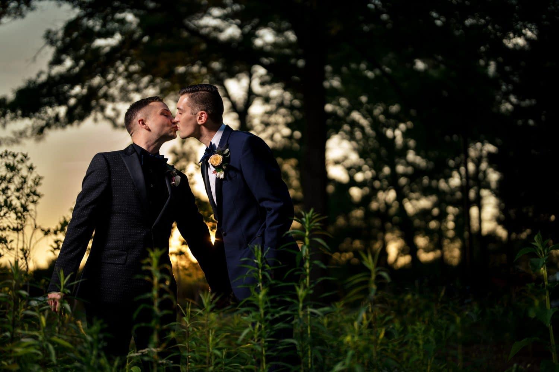 Kissing on the Bishop Farmstead Property during wedding photos shot by John Ryan