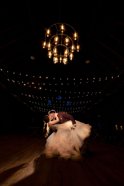 Beautiful bride and groom dancing under light display