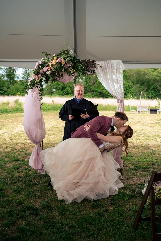Groom kissing bride at wedding at Bishop Farmstead Wedding shot by John Ryan
