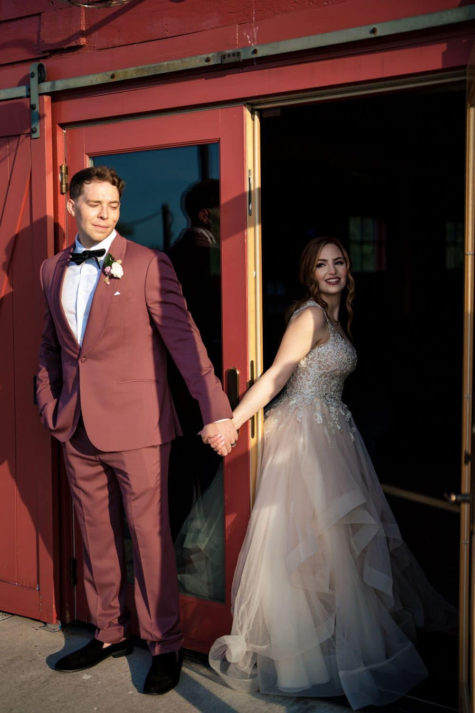 Gianna and Jon holding hands inside Red Barn house Bishop Farmstead Wedding shot by John Ryan