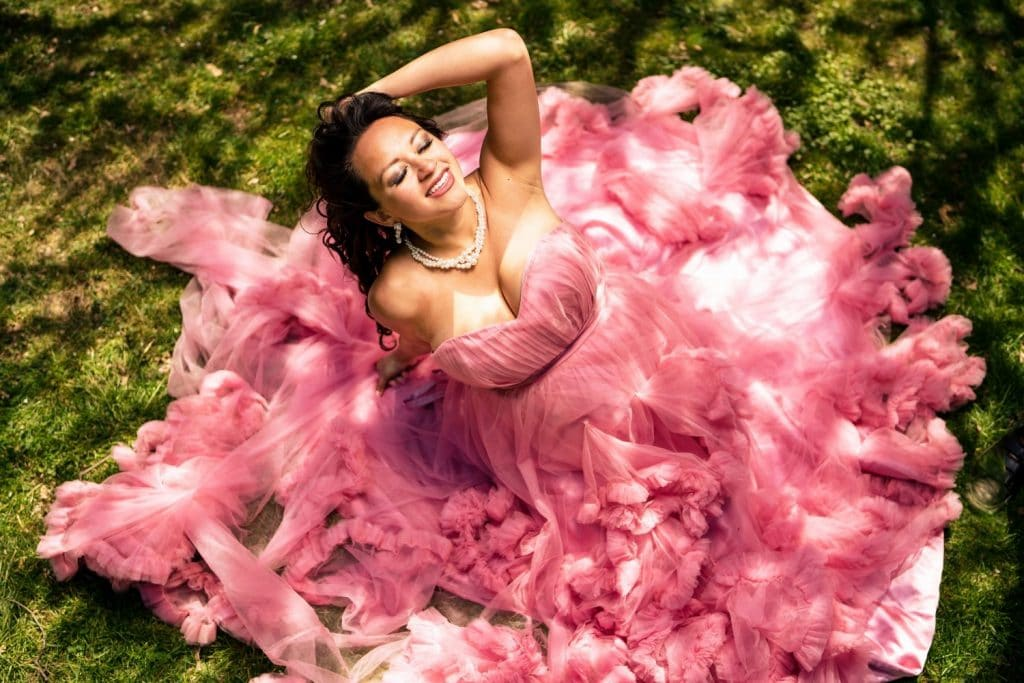 woman in pink dress sitting in grass taken from above