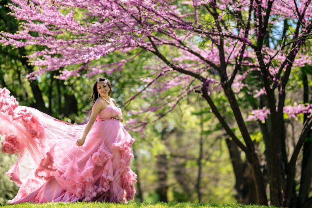 woman in pink dress under tree with pink blossoms