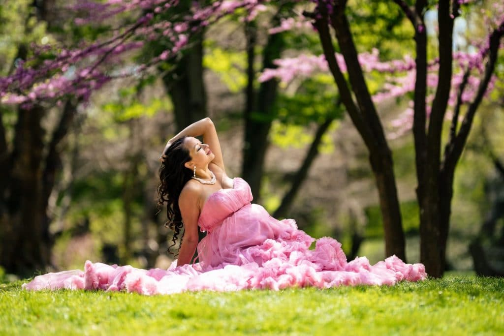 woman sitting in grass wearing a pink dress glamour shot