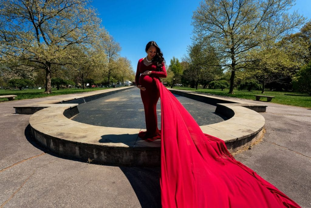mother standing on ledge wearing red dress