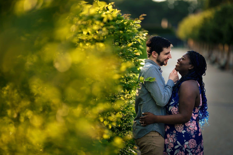 Happy couple hugging near bushes in Longwood Gardens Engagement Shot By John Ryan