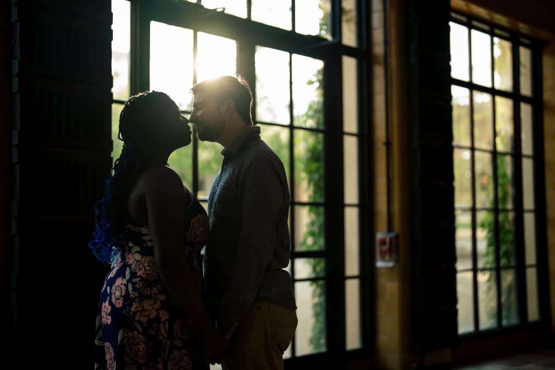 Romantic kiss near the double doors inside indoor gardens Longwood Gardens Engagement Shot By John Ryan