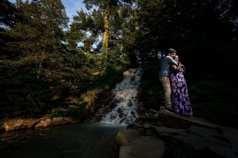 Hugging near the waterfall in the garden Longwood Gardens Engagement Shot By John Ryan