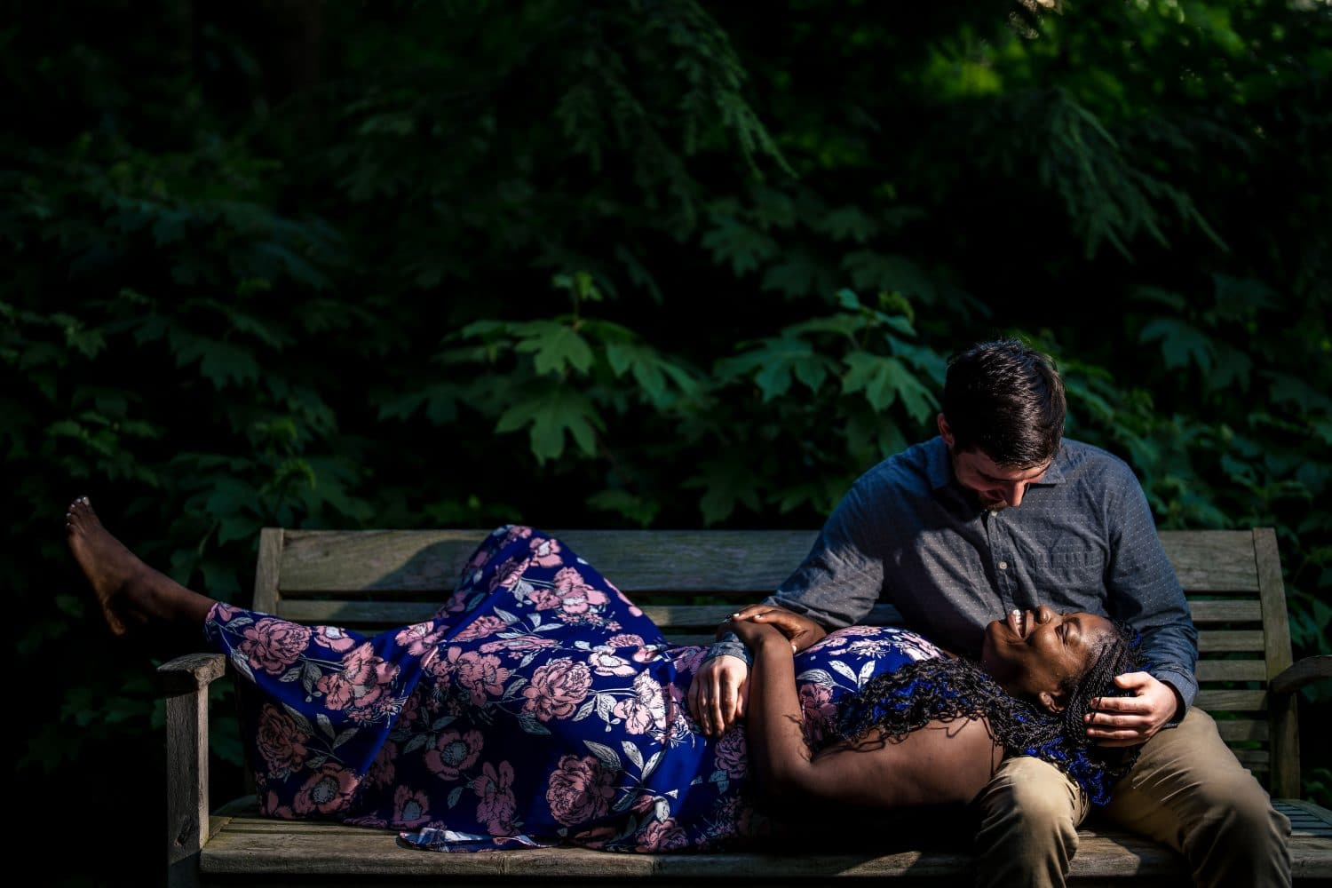 Dinah laying on the bench with Corey Longwood Gardens Engagement Shot By John Ryan