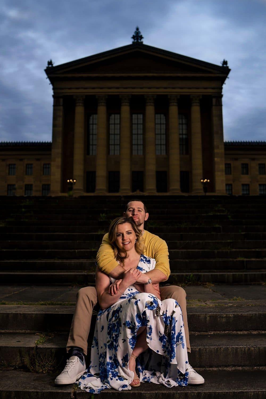 Couple sitting on the steps of the Philadelphia Museum of Art Philadelphia Engagement Session Shot by John Ryan