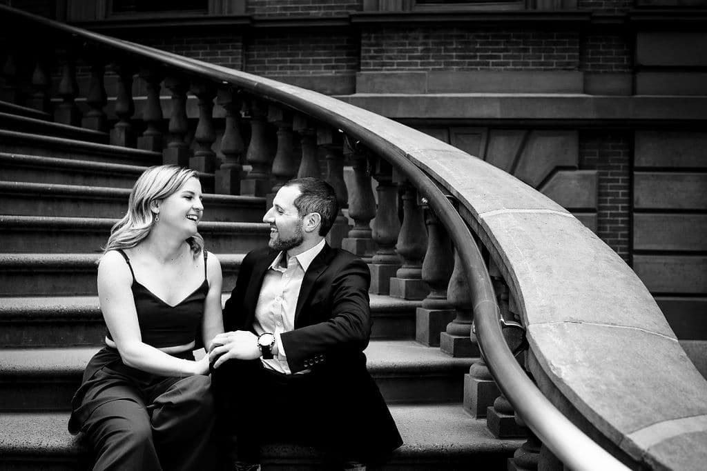 Black and white photo of couple sitting on the steps Philadelphia Engagement Session Shot by John Ryan
