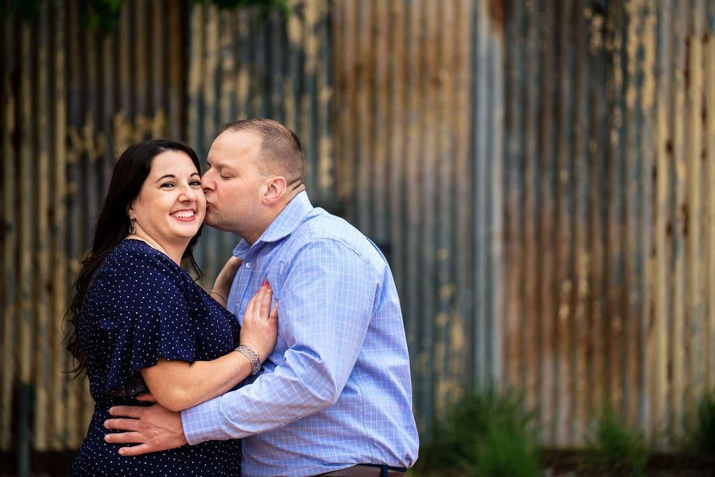 Guy kissing fiance on the cheek Philadelphia Navy Yard Engagement Session Shot by John Ryan