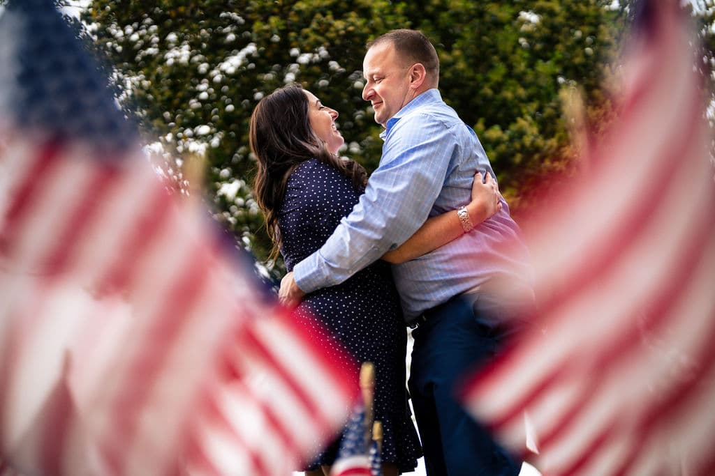 Navy seal and fiance near the American Flag embracing Philadelphia Navy Yard Engagement Session Shot by John Ryan