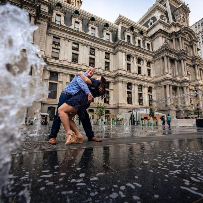 Dancing in the rain downtown Philly Philadelphia Navy Yard Engagement Session Shot by John Ryan