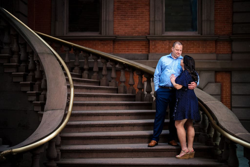 Couple on the staircase downtown philly embracing Philadelphia Navy Yard Engagement Session Shot by John Ryan