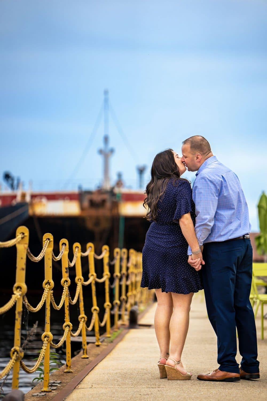 Couple smooching while at the Navy Yard Philadelphia Navy Yard Engagement Session Shot by John Ryan