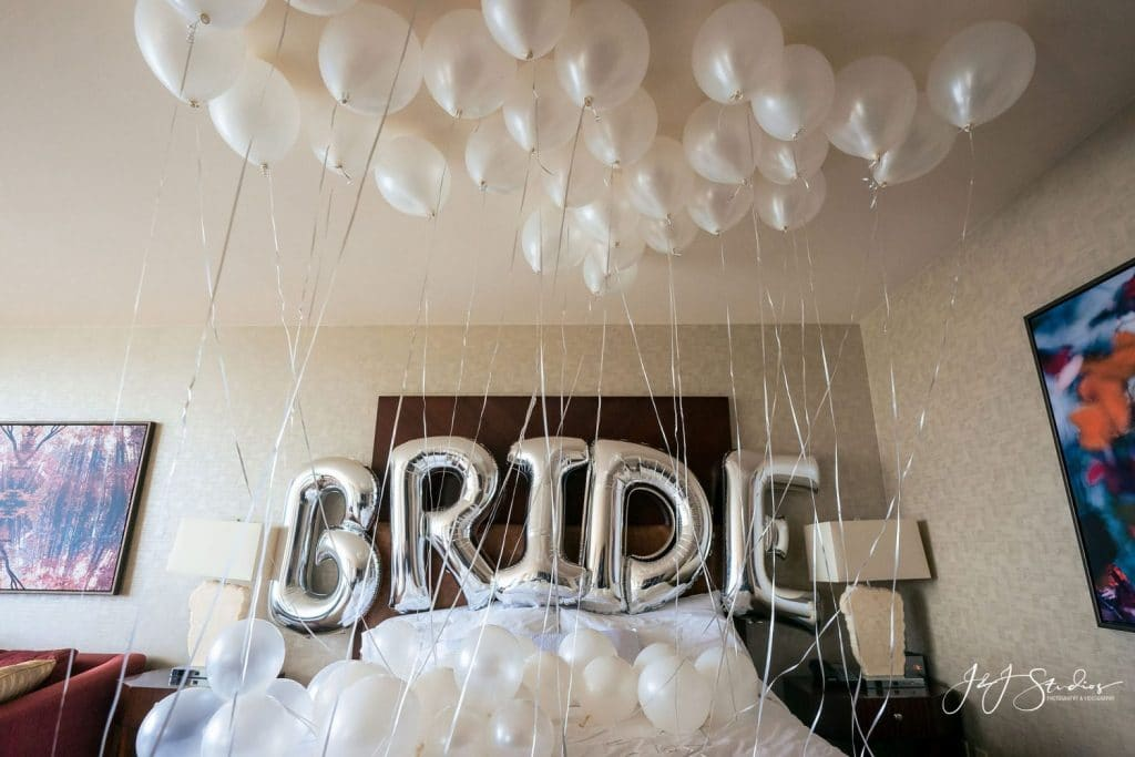 silver bride balloons on hotel bed