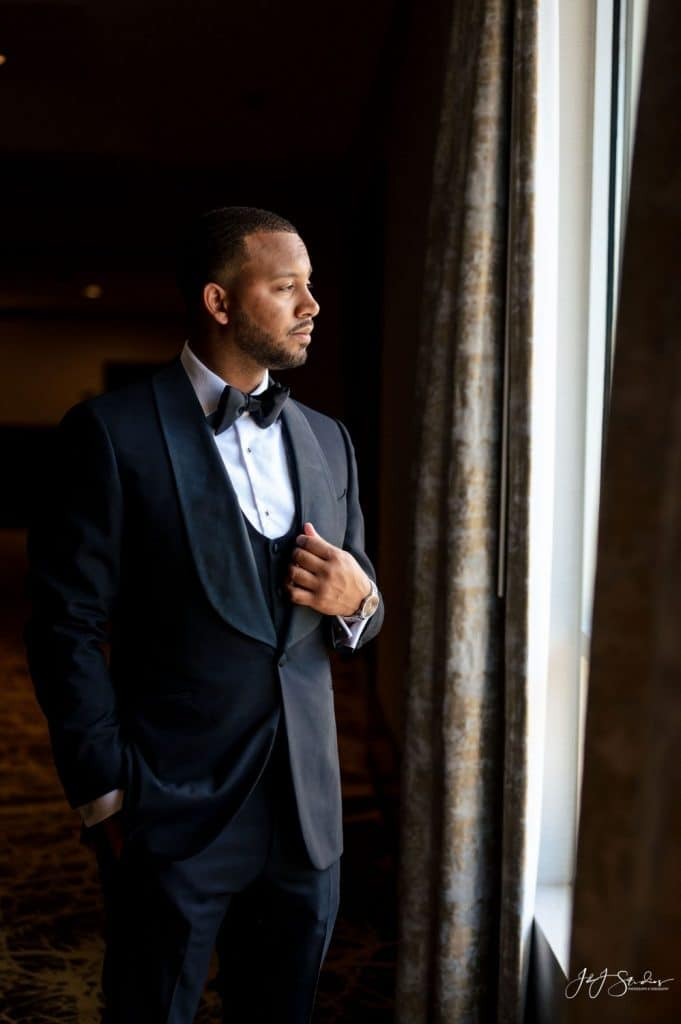 groom in black and white tuxedo dramatic
