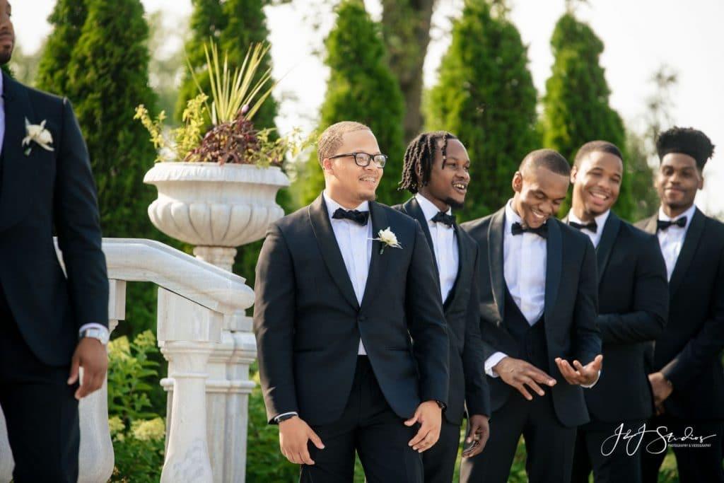 groomsmen in tuxedos outdoor wedding ceremony