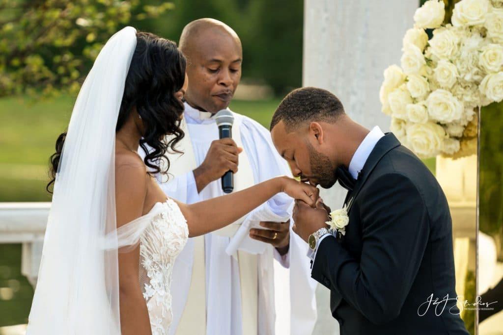 groom kissing bride's hand wedding ceremony