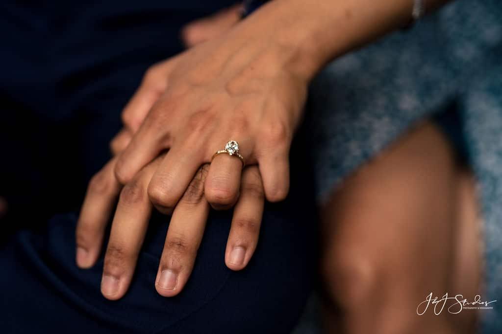 hands held together engagement ring