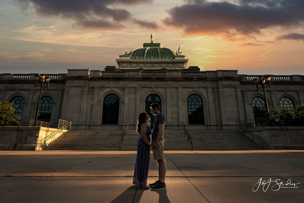omantic photo of couple embracing as the sun goes down in front of Philadelphia Museum of Art Shot By John Ryan