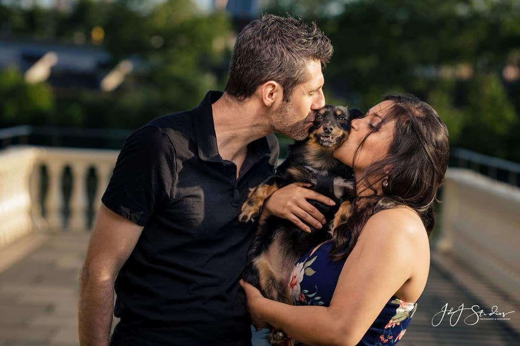 Dave and Robin kissing their cute dog at the park Shot By John Ryan