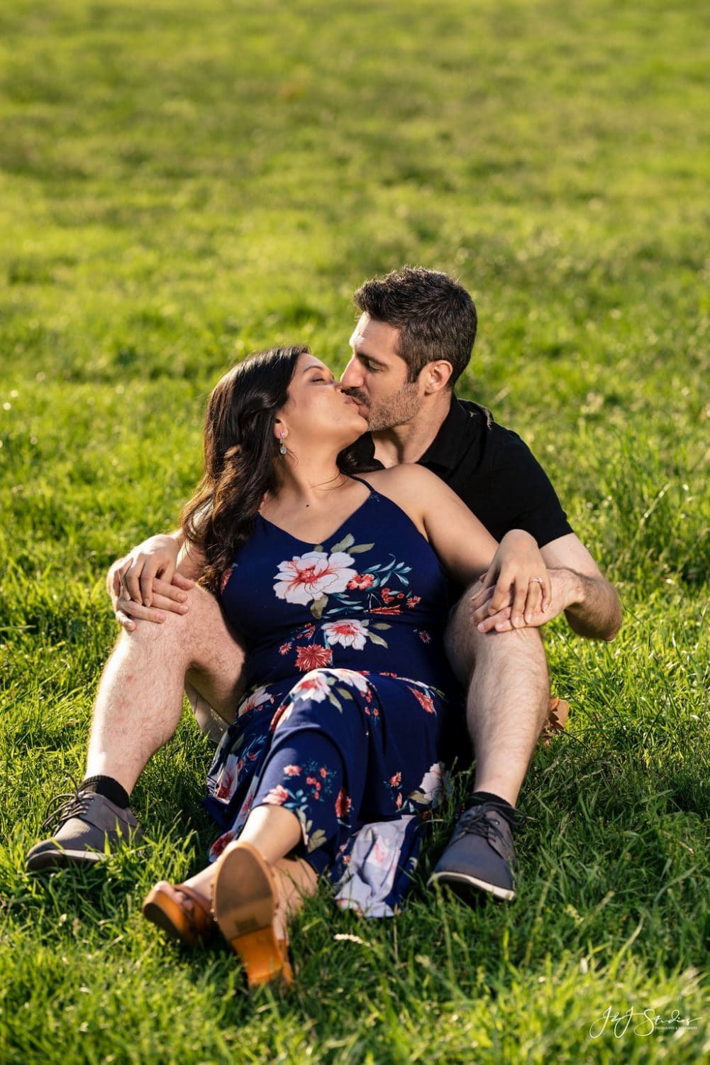Couple in love kissing in park on green grass Fairmount Engagement Shot By John Ryan