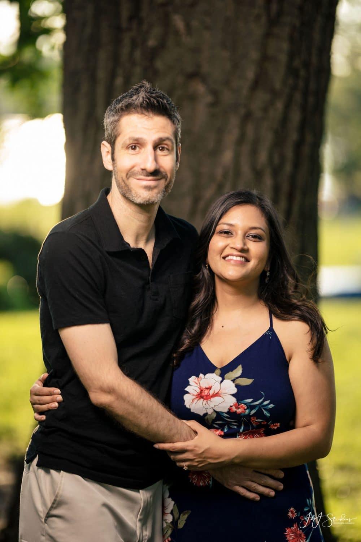 Couple smiling in front of treeFairmount Engagement Shot By John Ryan