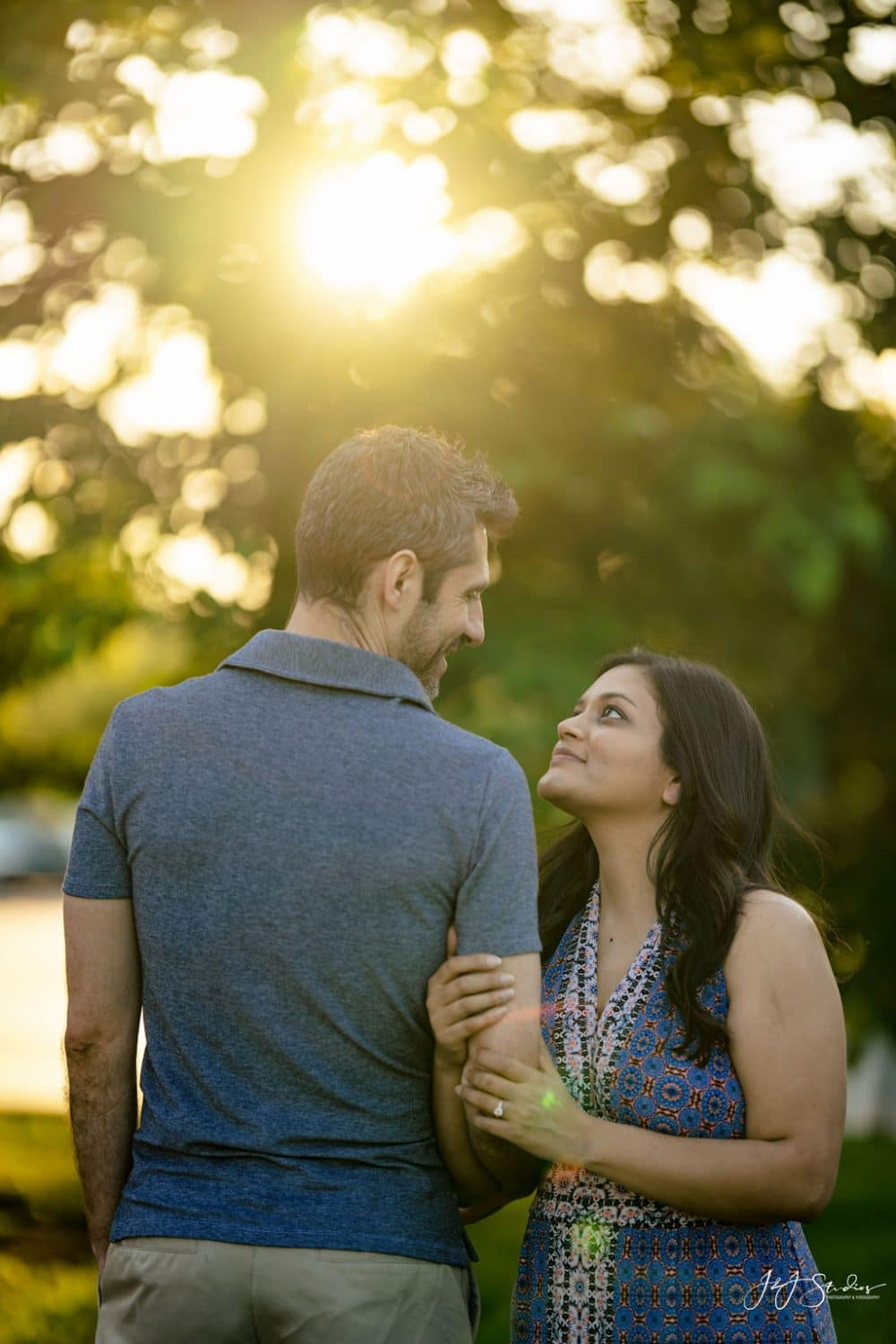 Couple in park embracing with the sun shining down Fairmount Engagement Shot By John Ryan