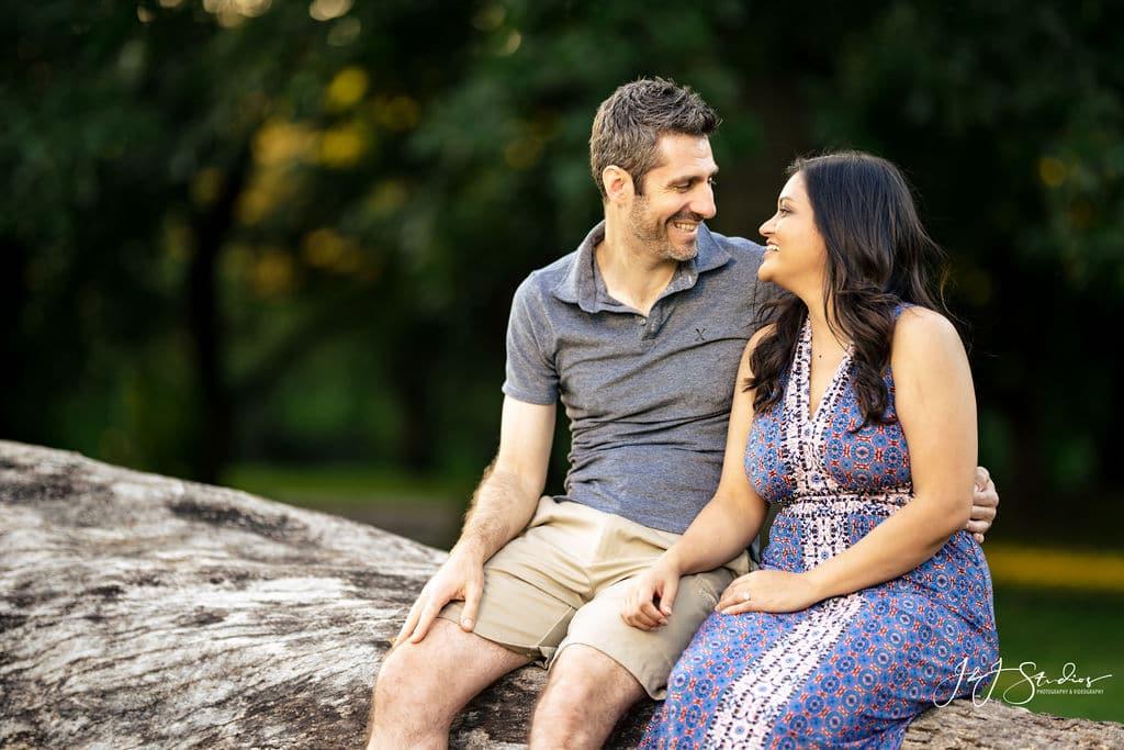 Couple sitting on the tree bark in park Fairmount Engagement Shot By John Ryan