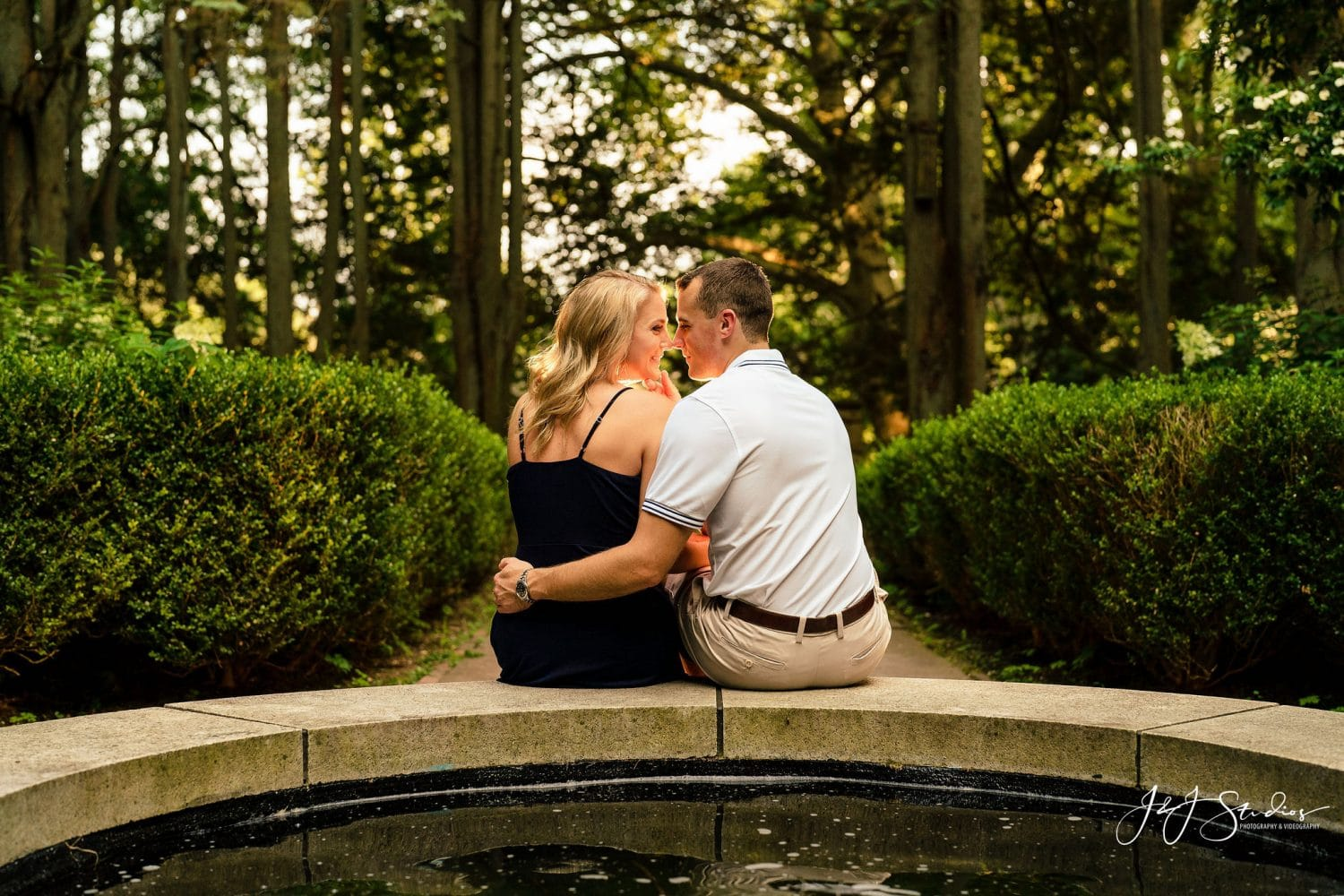 Couple sitting on park pond kissing Hunting Hill Mansion Engagement Shot By John Ryan