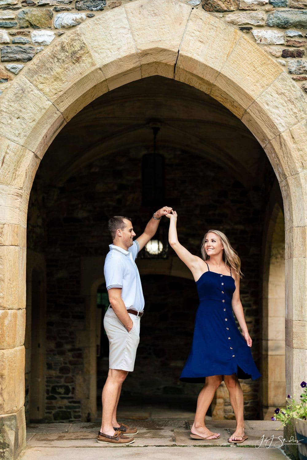 Couple dancing inside the arch at Ridley Creek State Park Hunting Hill Mansion Engagement Shot By John Ryan