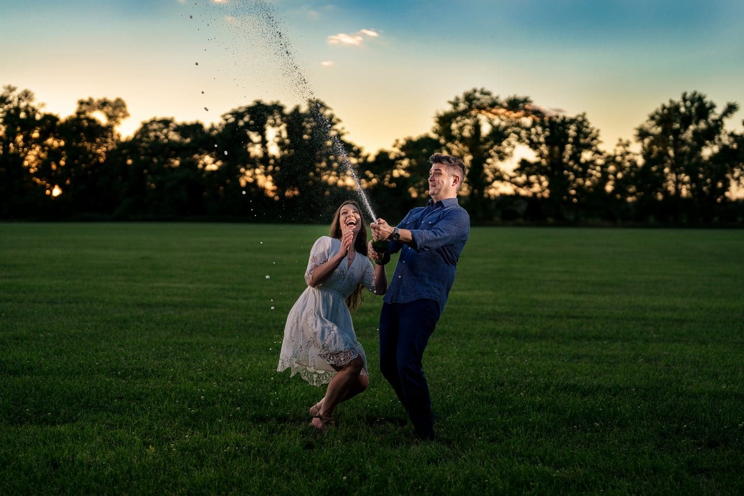 Couple popping champagne by J&J Studios