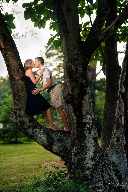 Couple climbing a tree by J&J Studios