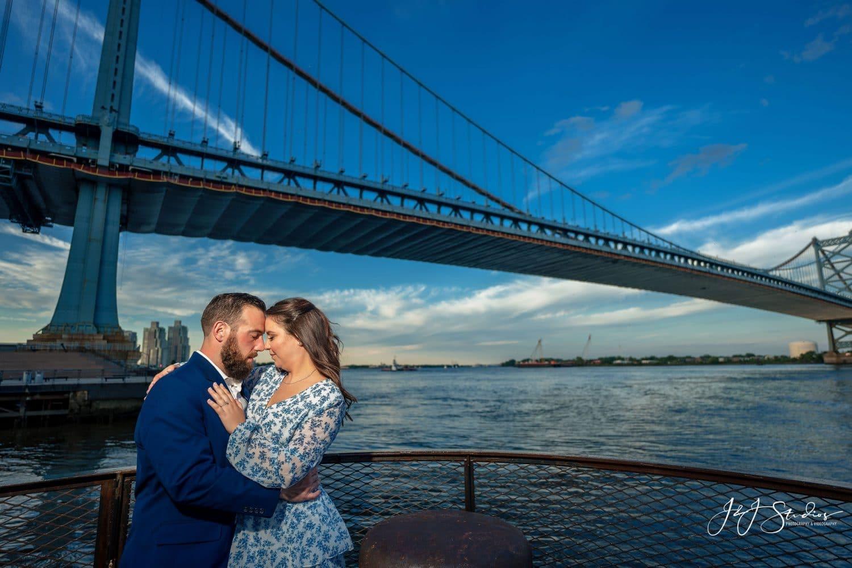 Couple standing in front of Benjamin Franklin Bridge