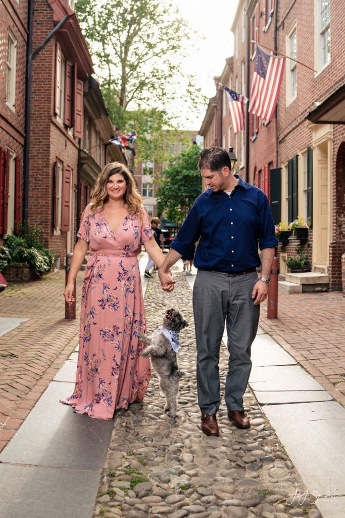 couple holding hands while dog stands against legs