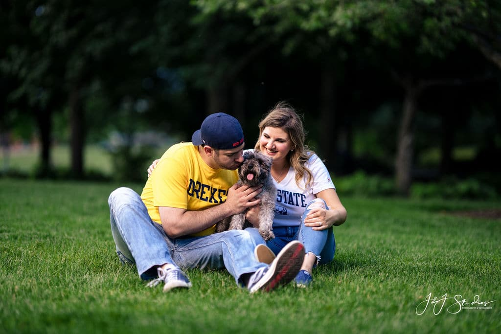 couple in college shirts sitting in grass with their small dog