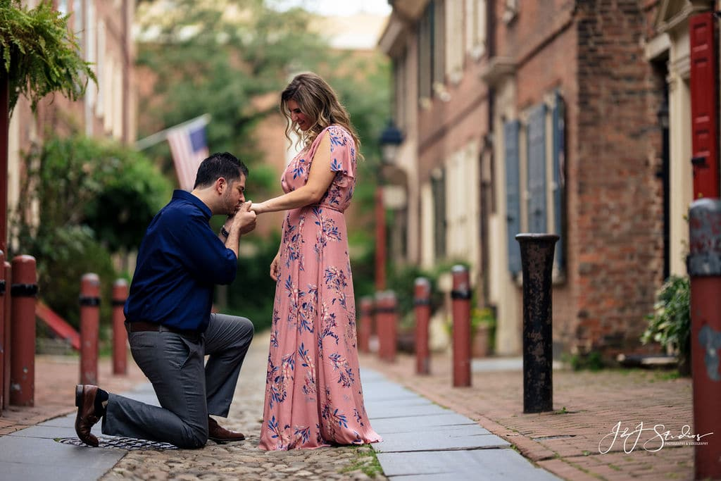 man kneeling and kissing woman's hand