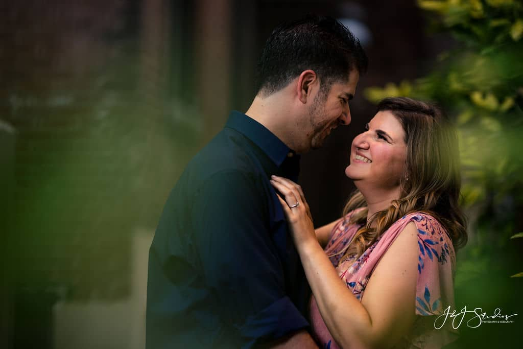 engaged couple smiling surrounded by leaves
