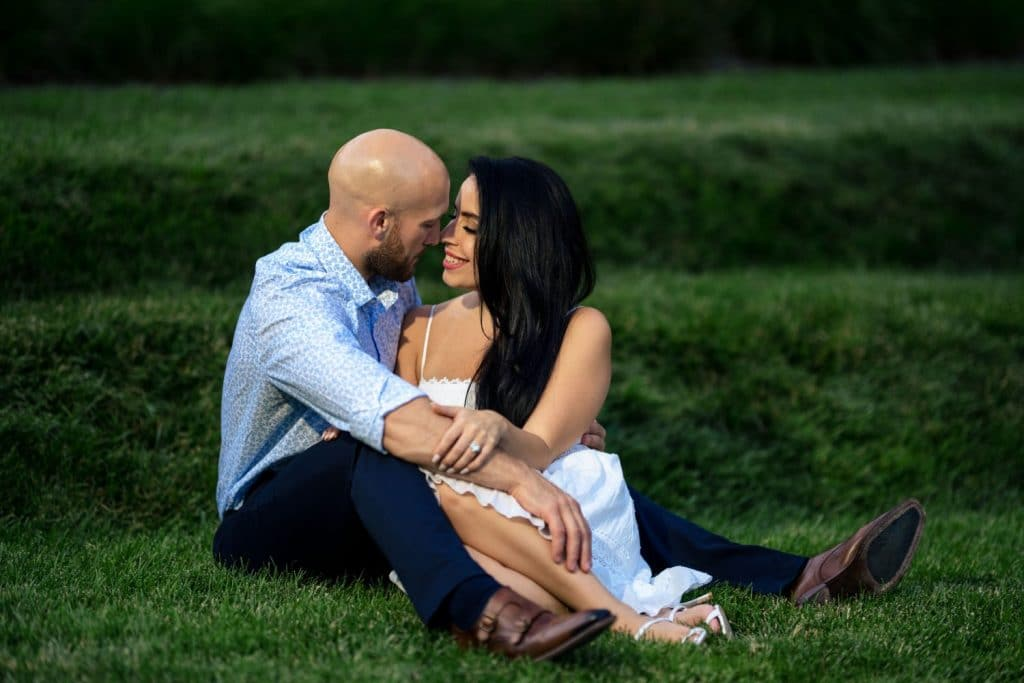 couple sitting in grass and about to kiss