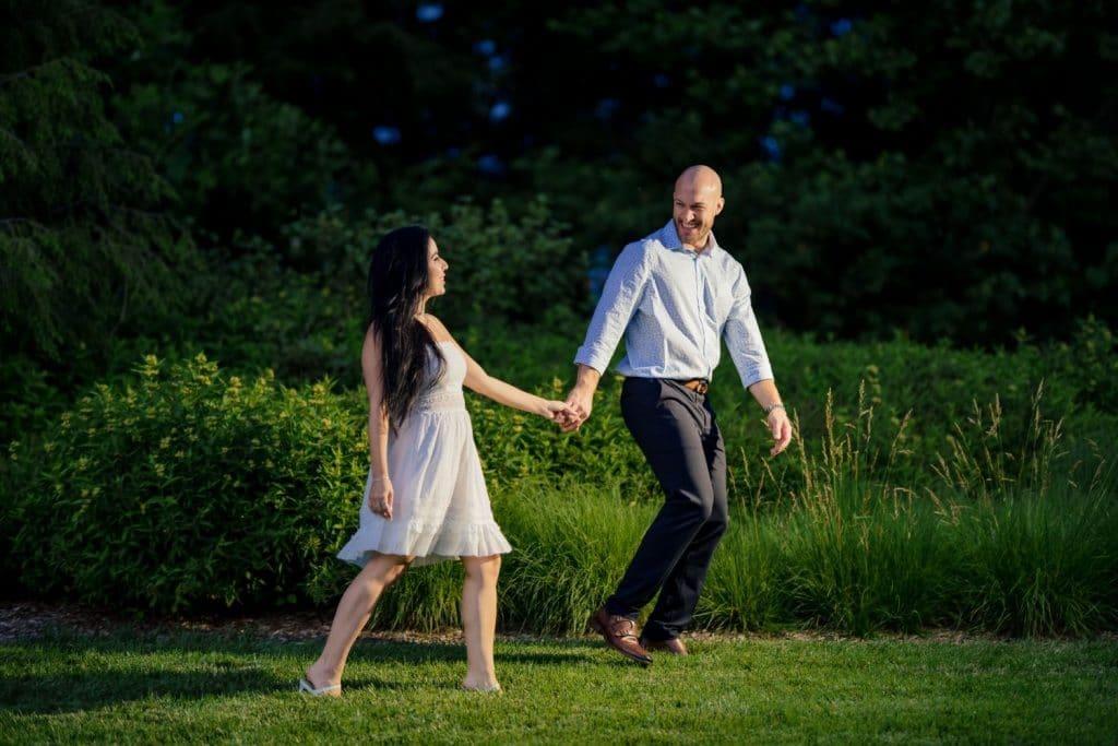 couple walking through grass holding hands