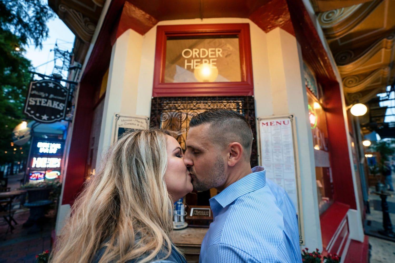 Kissing at Franklin Fountain during engagement shoot shot by John Ryan
