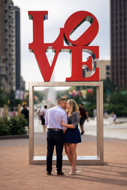 Under the Love sign at Philly Love Park Philadelphia Engagement Shot By John Ryan